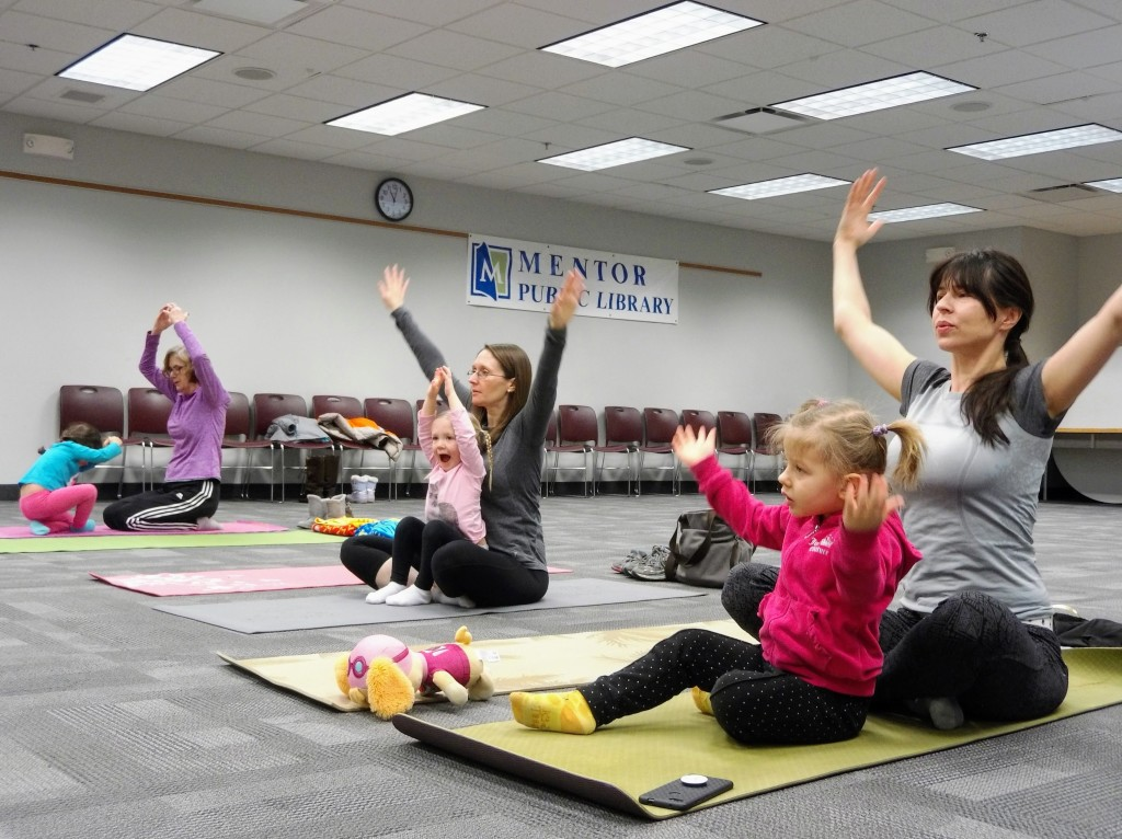 Families take a deep breath together during the Yoga Kids story time at Mentor Public Library.