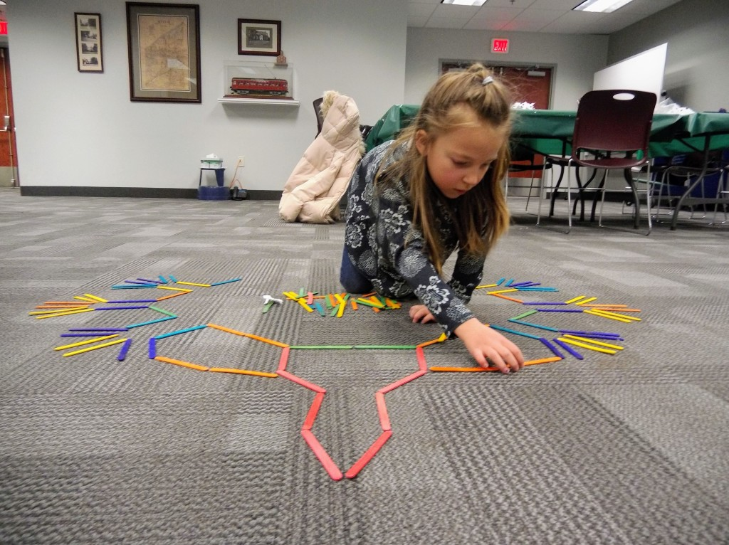 Children make enormous symmetrical snowflakes out of colored popsicle sticks at Mentor Public Library's STEAM program.