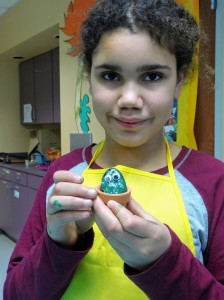 One of our young artists shows off her finished cactus pet rock.