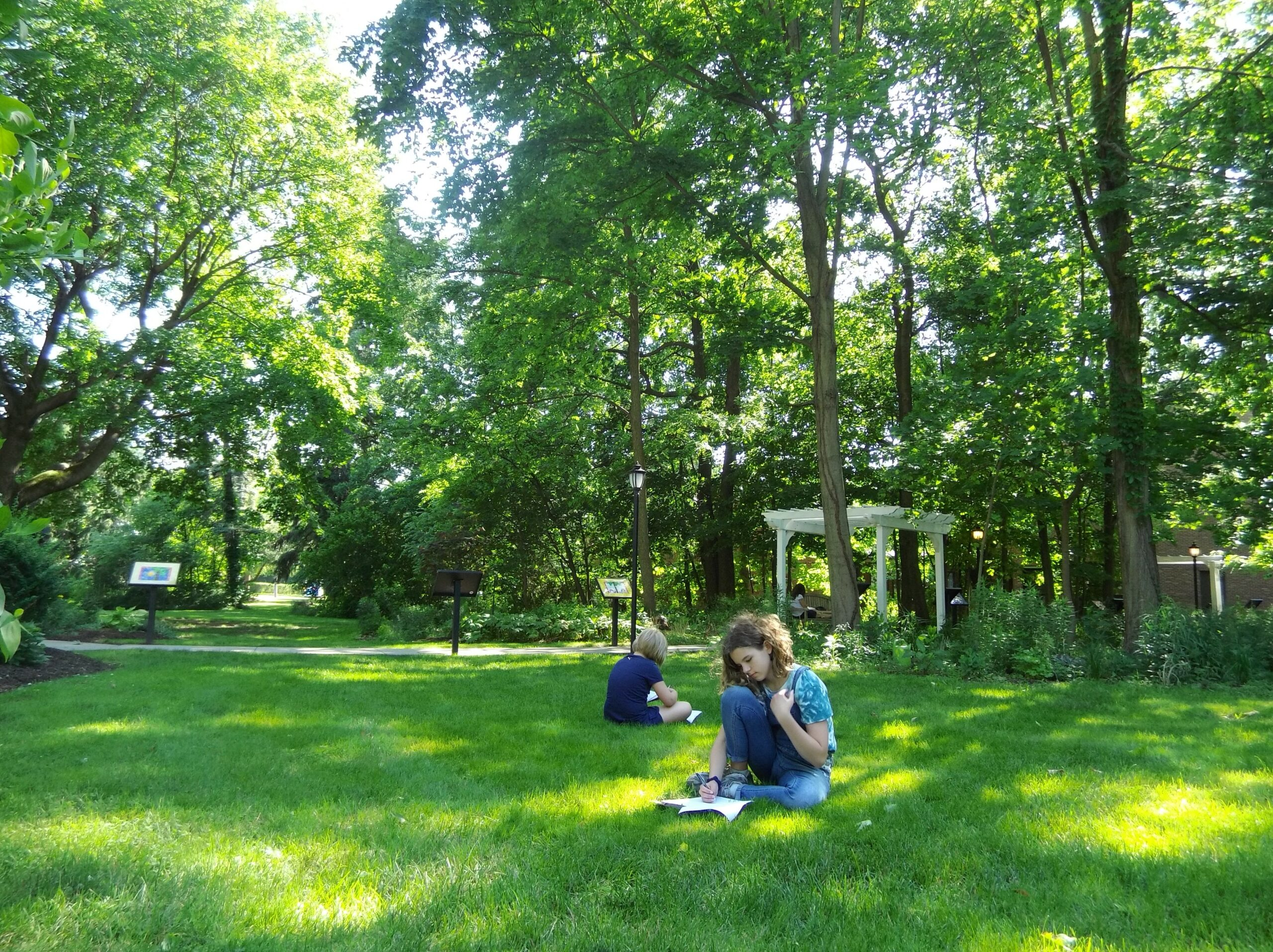 Teens Writing in journals while sitting on the Read Lawn.