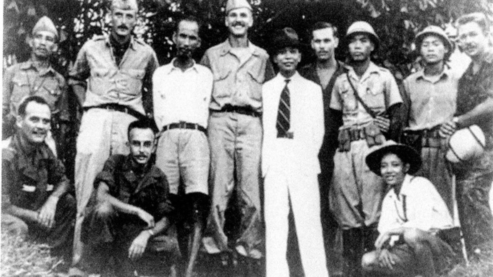 Group of American soldiers posing with 2 Indonesian men