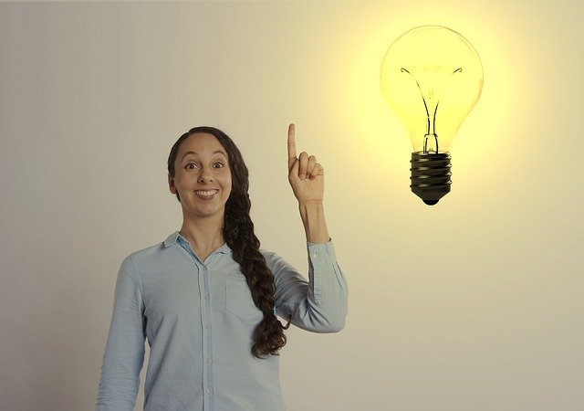 Woman with her hand raised and a light bulb next to her