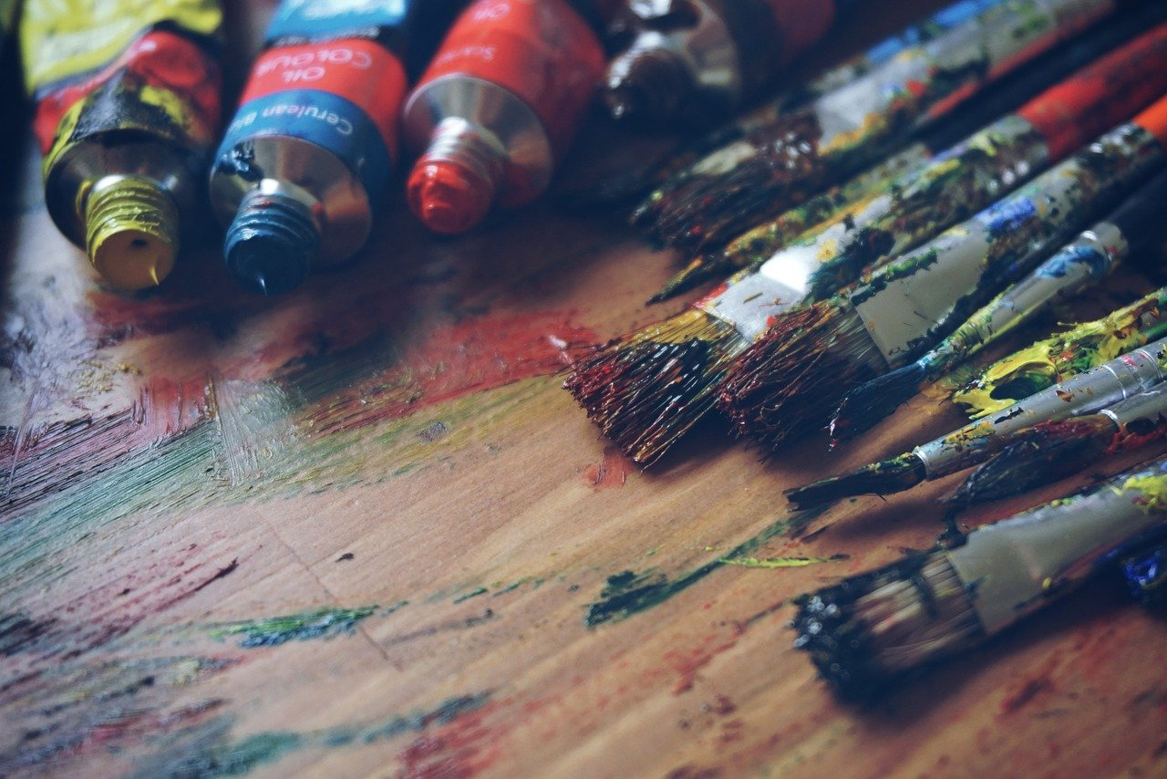 Messy tubes of paint and paint filled paintbrushes on a wooden desk