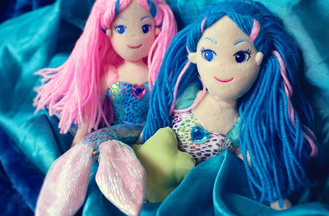 Two mermaid dolls one with pink yarn hair and one with blue.