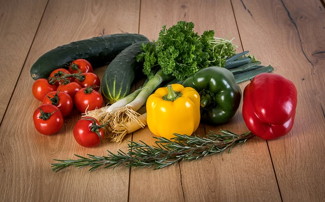 Pile of vegetables - tomatoes, cucumbers, green onions, and yellow, red, and green peppers.
